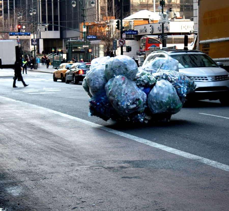 new york city 7th avenue person taking cans and bottles up the street