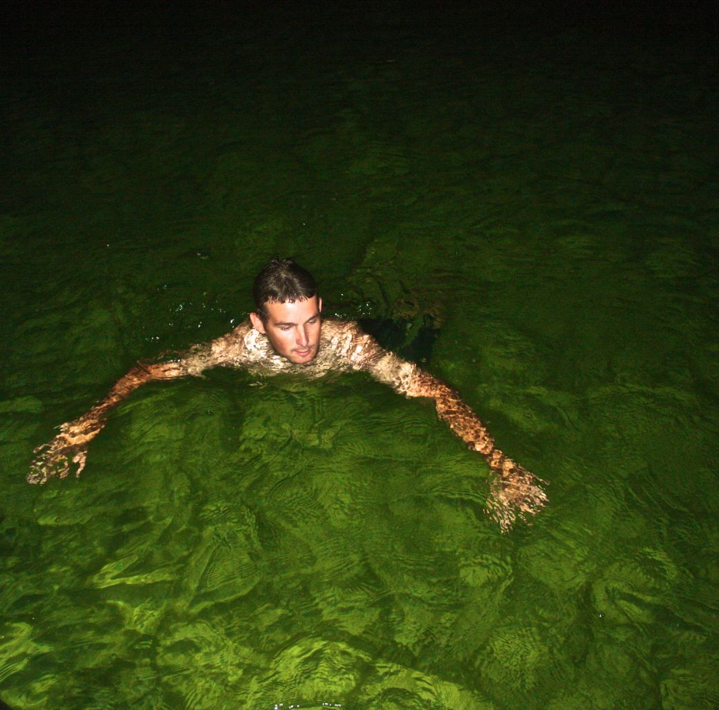 cayman islands boat guide swimming in green water
